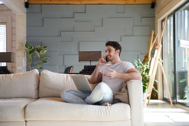 Человек на диване, используя телефон и ноутбук
