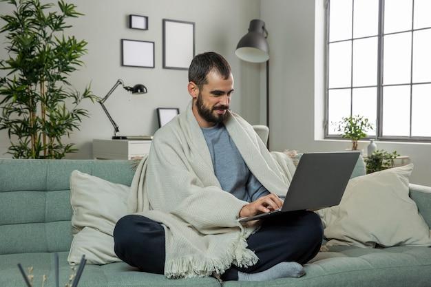 ノートパソコンで作業ソファの上の男
