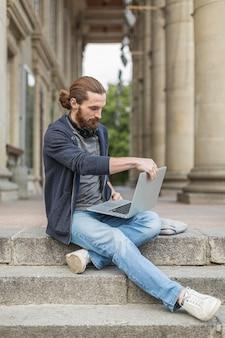Человек на шагах в городе работает на ноутбуке