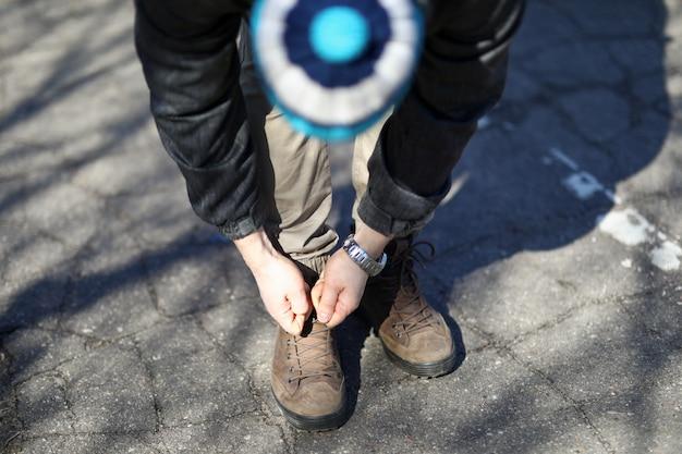 Мужчина на улице наклонился и завязал шнурки
