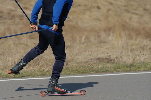 여름 스키를 탄 남자가 아스팔트 도로를 타고 있다.