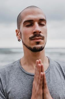 Человек на пляже, практикующий созерцание йоги