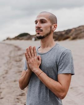 Человек на пляже практикует медитацию йоги
