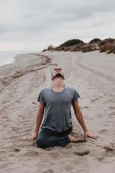 Человек на пляже практикует релаксацию йоги