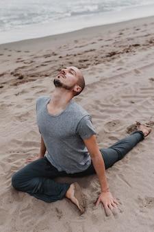 Человек на пляже практикует йогу