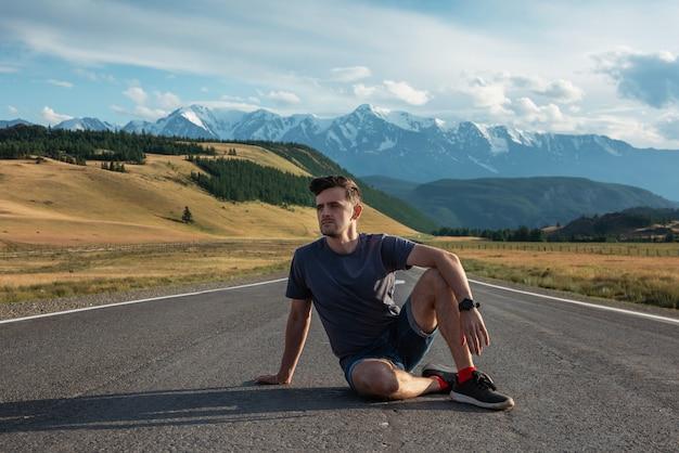 Человек на дороге чуйский тракт в горах алтая, одной из самых красивых дорог в мире