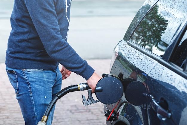 ガソリンスタンドの男が自分の車のタンクを満たしています