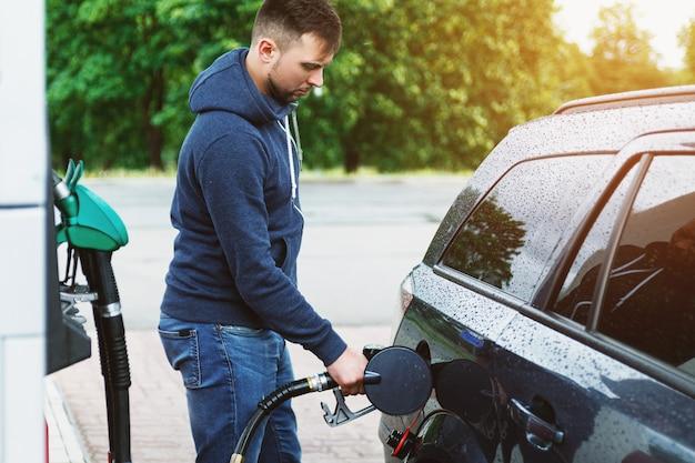 Мужчина на заправке заправляет бак собственной машины