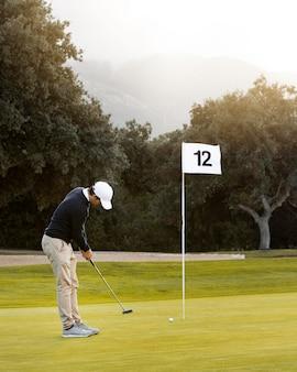 플래그 옆 재생 골프 필드에 남자