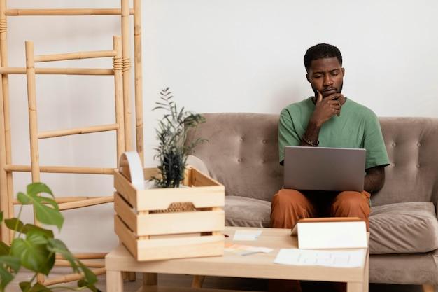 노트북을 사용하여 집을 재 장식하는 계획을 세우는 소파에 남자