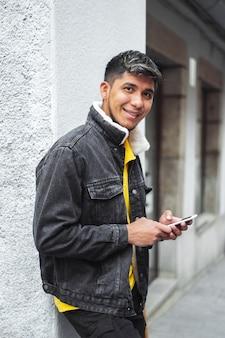 カメラを手に携帯電話を持って街の通りの男