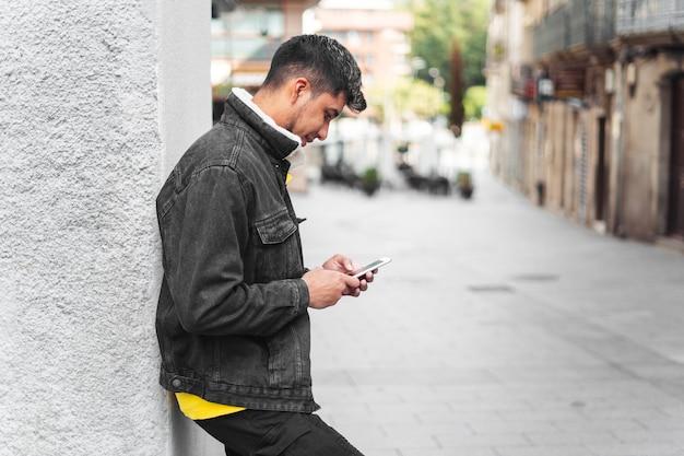 カメラを見ている手に電話を持っている街の通りの男携帯電話を見ている通りのラティーノ男