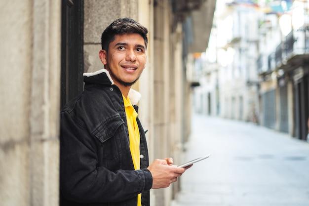 携帯電話を手にカメラを見ている街の通りの男ラティーノタブレットを手にまっすぐ前を見ている通りの男