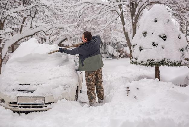 冬の日の路上で男は雪の車をクリアします