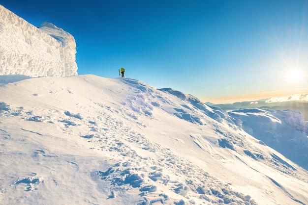 日没時の雪の中で冬の山の頂上に男