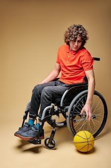 孤立した孤独な雰囲気の中で車椅子の男、スポーツマンはバスケットボールに従事したいです。怪我、落胆、絶望の概念 Premium写真