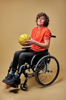 車椅子の男性は、黄色いバスケットボールのボールを持って、筋肉を強化するためにボールをプレーしています。障害者のライフスタイル、孤立したベージュの背景