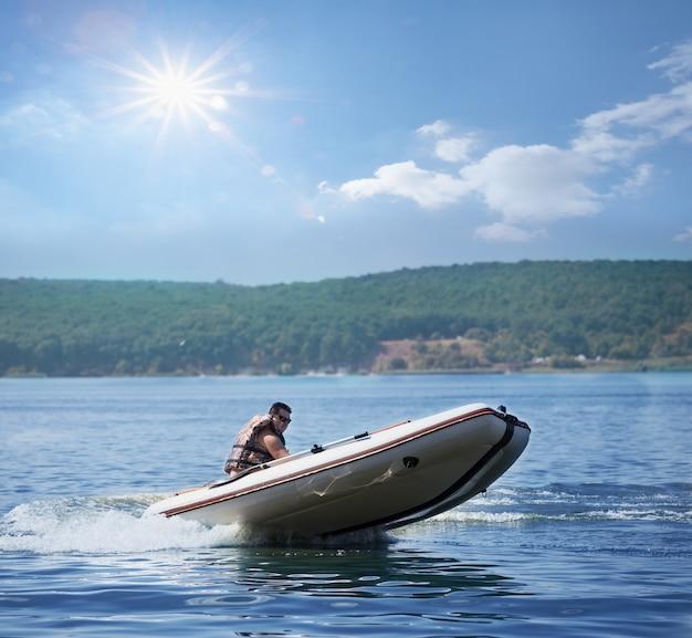 白の膨脹可能なモーターボートの男