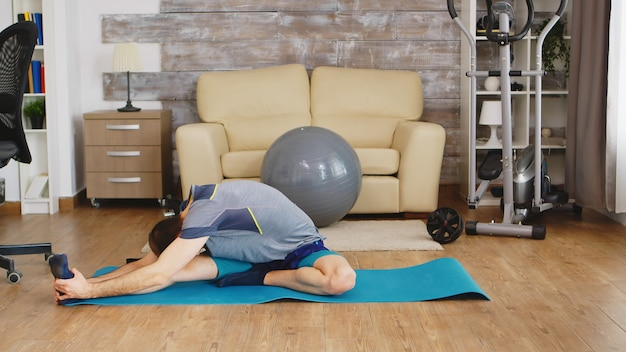 居間で運動する前に彼の体を伸ばすヨガマットの男。