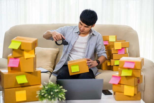 Man online entrepreneur using tape to packing parcel box at home office, prepare product for deliver to customer