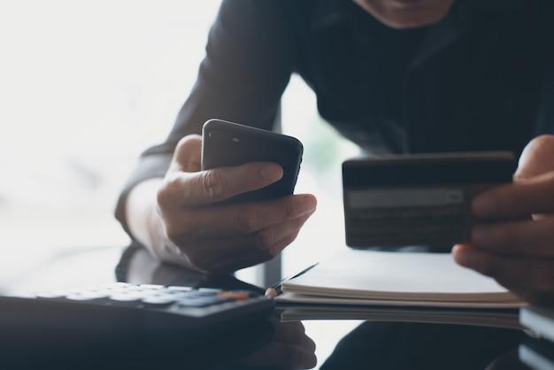 男のオンラインショッピングとスマートフォンのバンキングアプリでインターネット決済による支払い