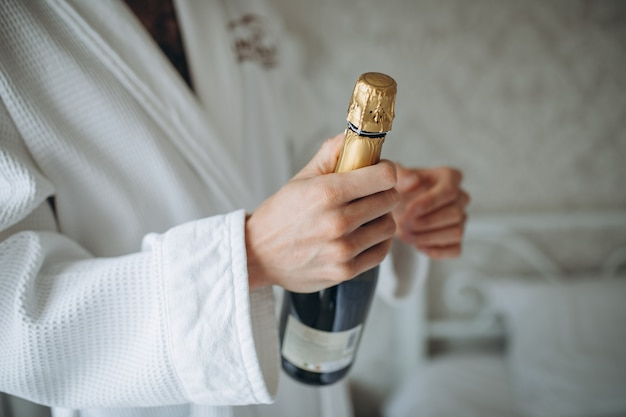 Человек открывает бутылку шампанского на белом фоне