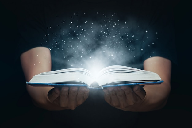 Man opened a magic book with growing lights and magic powder. learning and education concept