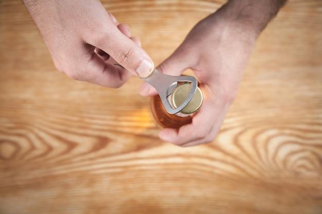 木製のテーブルでビールのボトルを開く男。