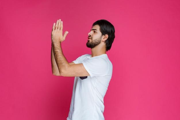 남자는 무언가를 위해기도하기 위해 손을 열고 결합합니다.