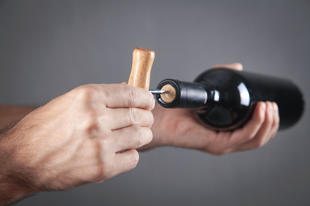 Мужчина открывает бутылку вина со штопором.