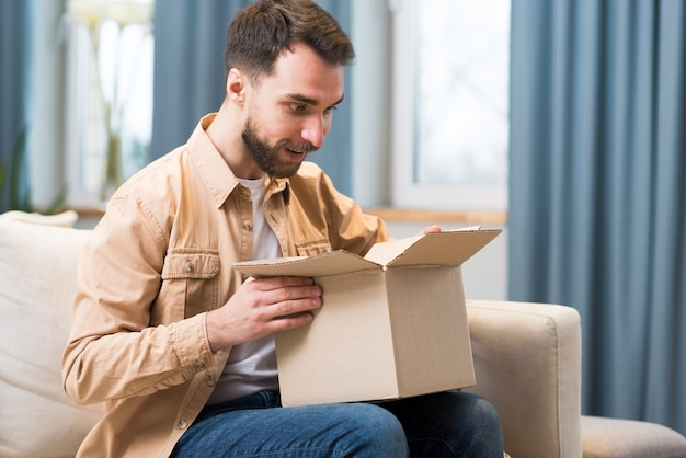 Man opening box of good he ordered online