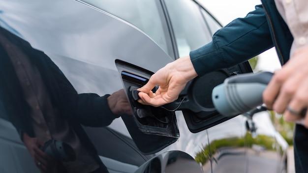 Uomo che apre la presa di ricarica dell'auto e tiene il caricabatterie alla stazione di ricarica