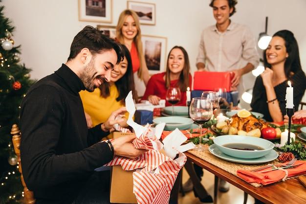 Man opening gift box at christmas dinner