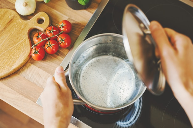 Человек открывает крышку кастрюли, готовит