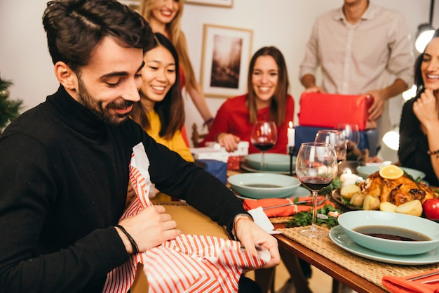 Man opening present box at christmas dinner
