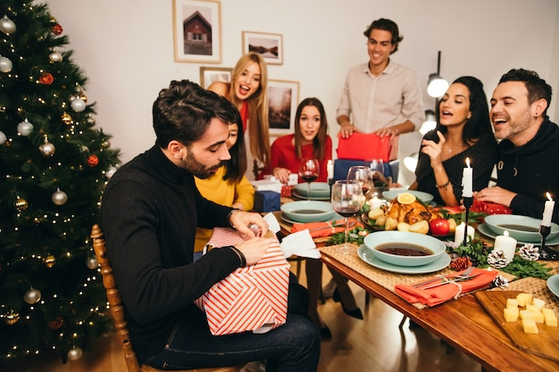 Man opening present at christmas dinner