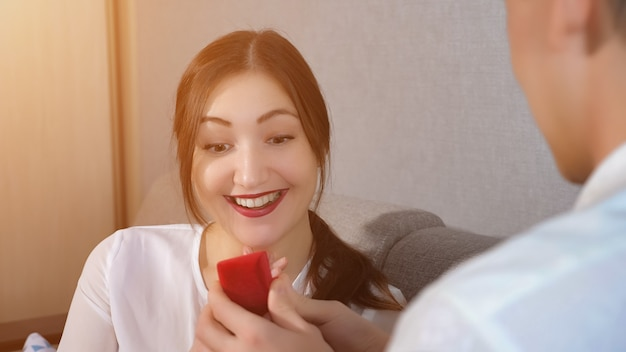 Man opening ring box, making offer, sunlight. attractive grateful girl with red lips looking surprised, sunlight