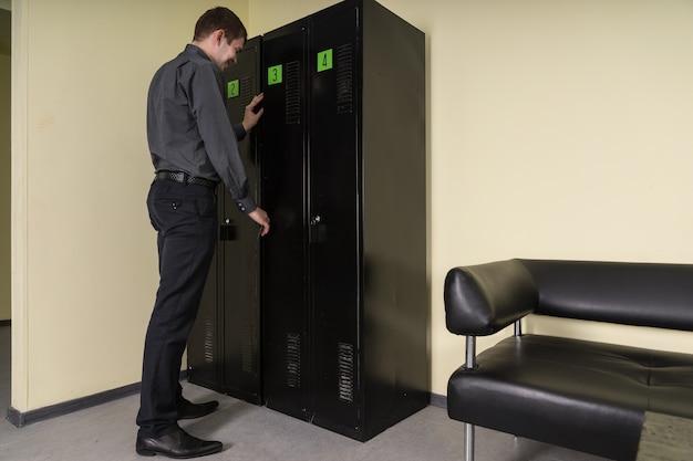 문에 두 개의 녹색 레이블이 있는 검은색 금속 파일 캐비닛 또는 찬장의 문을 여는 남자, 뒤에서 보기