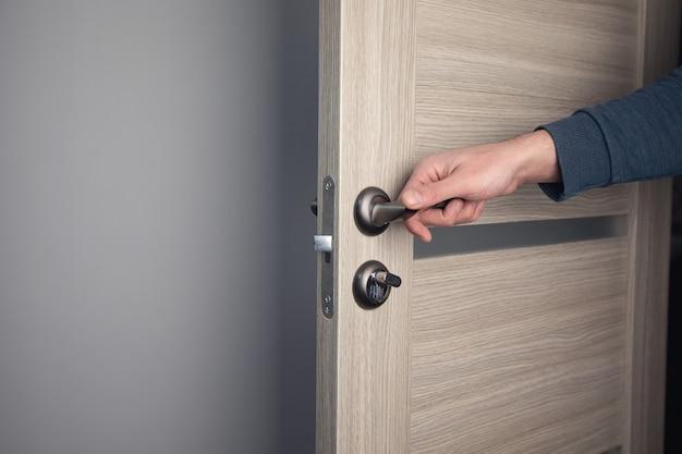 Человек открывает деревянную дверь в комнате