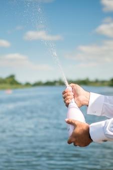 Мужчина открывает бутылку шампанского с брызгами