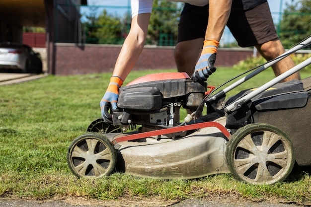 Man opens the fuel tank cap of lawn mower to refuel
