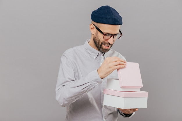 Man opens gift box, looks curiously, wears glasses, hat and white shirt, stands against grey background