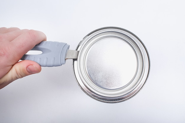 A man opens a jar of white paint with a can opener. renovation concept.
