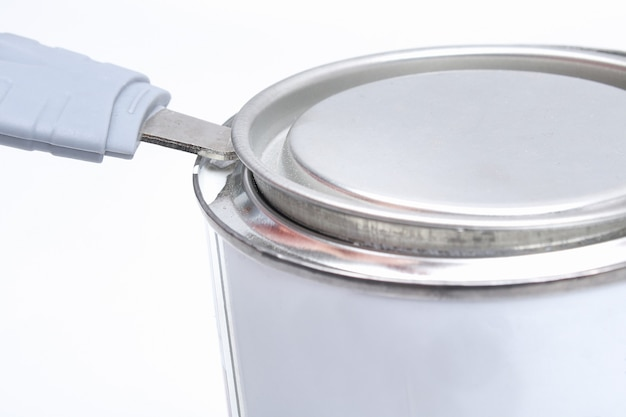 A man opens a jar of white paint with a can opener