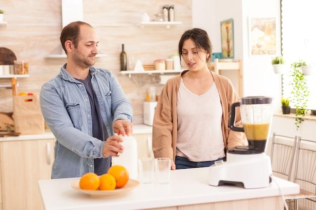 男はガールフレンドと話している間、栄養価の高いスムージーのために牛乳瓶を開けます。健康的なのんきで陽気なライフスタイル、食事を食べ、居心地の良い晴れた朝に朝食を準備する