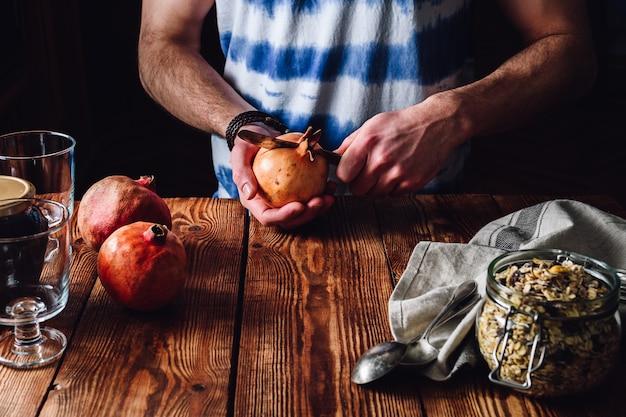 男はナイフでザクロを開きます。