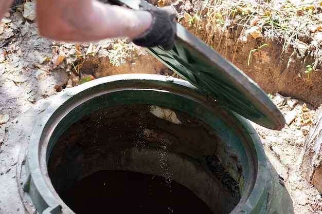 The man opens a sewer hatch. septic tank inspection and maintenance.