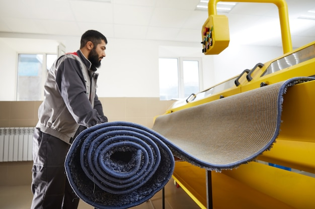 Man operating carpet automatic cleaning machine in professional laundry service