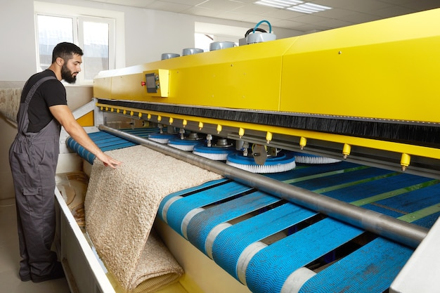 Man operating carpet automatic washing machine in professional cleaning service