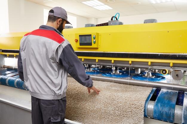 Man operating carpet automatic washing machine in professional laundry service